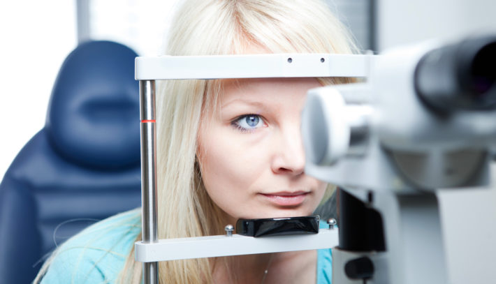 optometry concept – pretty young woman having her eyes examined